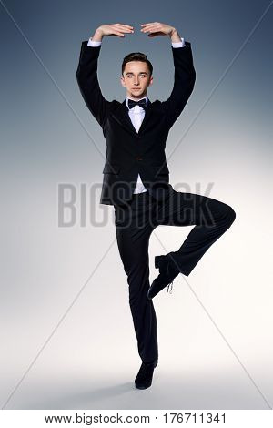Elegant young man dancer in black suit and bow-tie posing at studio. Male ballet dancer.
