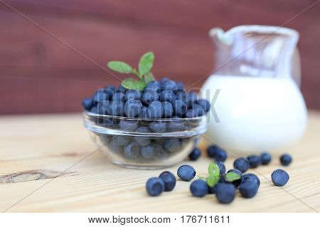 Blueberry on wooden background. Blueberry close up and blueberry background. Berries closeup. Blueberry with milk