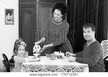 A family of three in the interior of the fifties of the last century, drinking tea for lace tablecloth vintage oak table.Black-and-white photo. Retro style.
