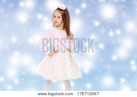 Dressy little girl long blonde hair, beautiful pink dress and a rose in her hair.She keeps hands on hips.Blue Christmas festive background with white snowflakes.
