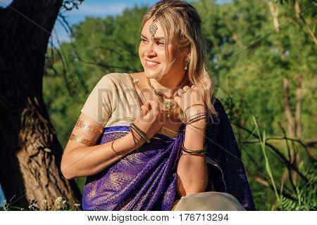Beautiful european woman in traditional indian sari near the lake