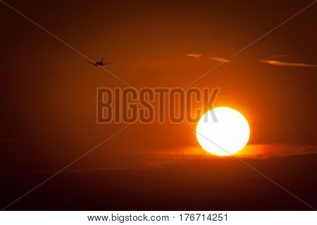 Beautiful sunset with airplane flying away