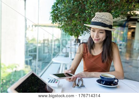 Woman pay the bill by mobile phone in coffee shop, NFC payment concept