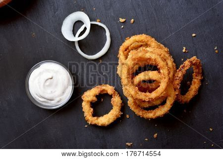 Crunchy fried onion rings and white sauce on dark background top view