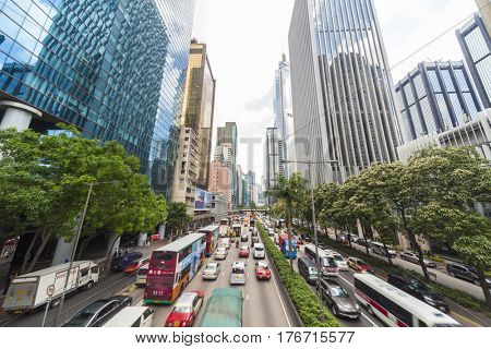 HONG KONG - May 28 2015: Motion Blurred cars, traffic and taxis driving through skyscraper office buildings, May 28, 2015 in Hong Kong.