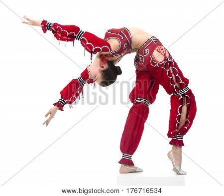 A young girl in stage costume shows gymnastics. Studio shooting stage performances on a white background. The isolated image.