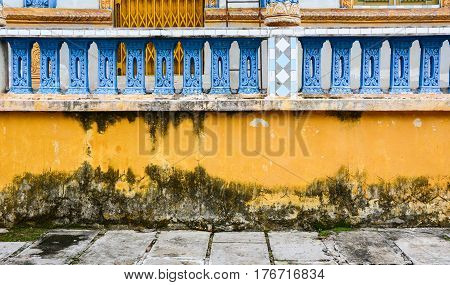 Yellow old wall with decorations at the ancient Khmer Buddhist temple.