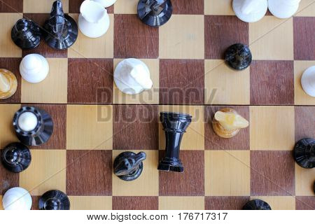 Black chess piece on the board fell surrounded by three different horses top view / unexpected denouement Party