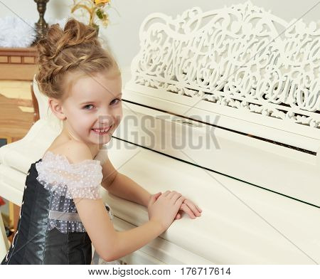 Little girl 7 years, elegant Princess dress , is sitting at an old white grand piano.The girl put a hand on the lid of the instrument.