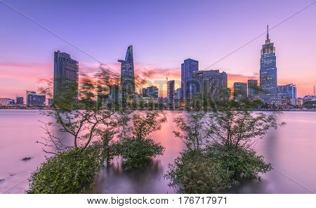 Ho Chi Minh City, Vietnam - March 9th, 2017: Riverside City sunset clouds in the sky at end of day brighter coal sparkling skyscrapers along beautiful river in Ho Chi Minh City, Vietnam