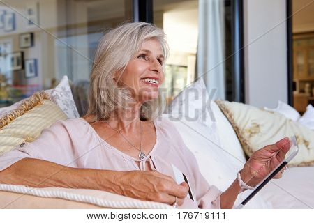 Close up portrait of older woman with tablet and credit card in living room