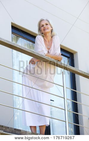 Beautiful Older Woman Leaning On Terrace Railing Smiling