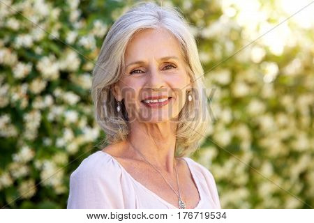 Portrait Of Happy Older Woman Standing Outside In Summer
