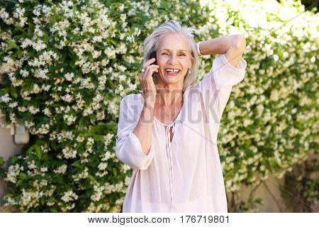 Older Woman Talking On Phone With Hand In Hair Outside
