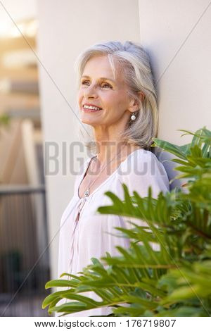 Older Woman Leaning On Wall Outside Smiling