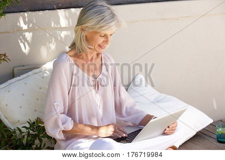 Relaxed Older Woman Outside With Laptop