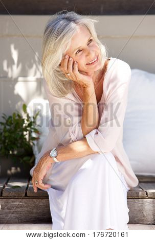 Older Woman Smiling And Sitting On Porch Outside