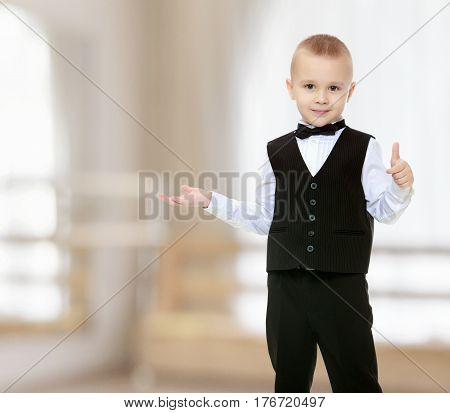 Beautiful little blond boy in a fashionable black suit with a tie.He shows his hand to the side.In a room with a large semi-circular window.