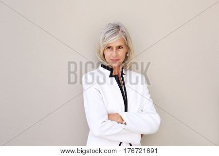 Portrait of beautiful older woman staring and standing with arms crossed poster