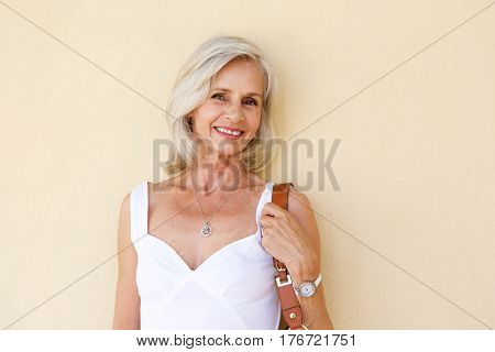 Happy Older Woman Standing In Spring Dress With Purse