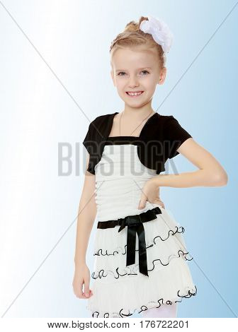 Beautiful little blonde girl dressed in a white short dress with black sleeves and a black belt.Closeup.On the pale blue background.