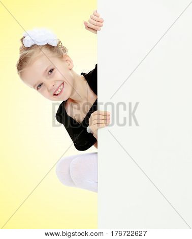 Beautiful little blonde girl dressed in a white short dress with black sleeves and a black belt.The girl peeks out from behind white banner.On a yellow gradient background.