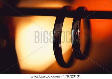 Classic gold wedding ring hung on a background of fire. red colour. macro