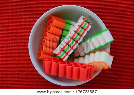 Horizontal image of bright red background with white bowl filled  with Christmas ribbon candy.