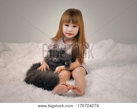 Little girl with luxurious red hair in bed with a cat