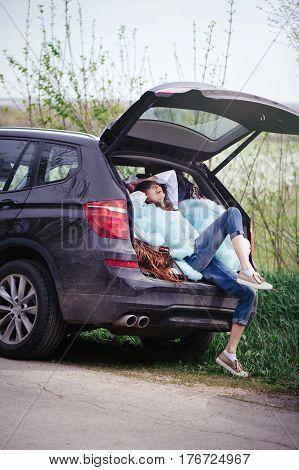 Beautiful Woman Sitting In The Car Trunk