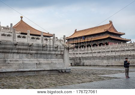 Beijing, China - Oct 30, 2016: Marble balustrades on tiered terraces near a palace in the Forbidden City (Gu Gong, Palace Museum). A man uses his cellphone. Note the ornate roof architecture.