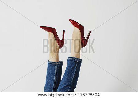 Female legs in burgundy heels on a white background