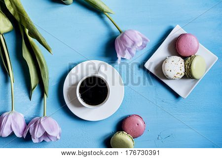 Cup of coffee with pastry and flowers on a blue table top view
