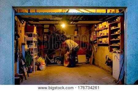 Istanbul, Turkey - March 1, 2012: Man tidying up his tools at his garage at night
