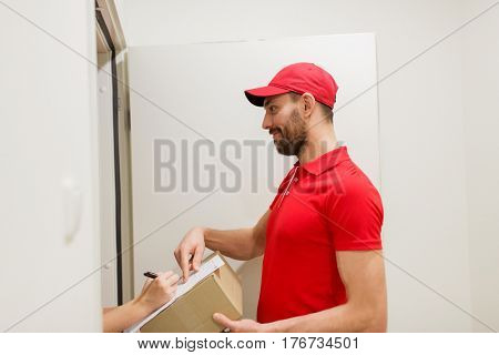 delivery, mail, people and shipping concept - happy man with box and customer signing form at home