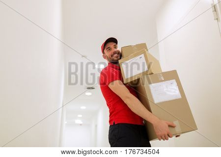 delivery, mail, people and shipment concept - happy man in red uniform with parcel boxes in corridor