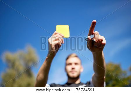 sport, caution, game and people - referee with whistle showing yellow card on football field