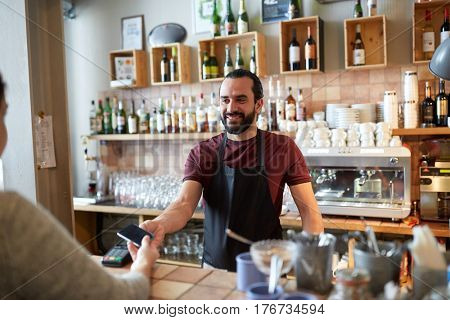 small business, people and service concept - happy man or waiter in apron with card reader and customer with smartphone paying at bar of coffee shop