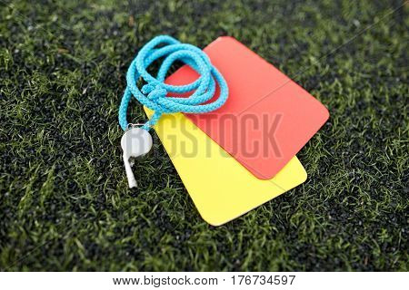 sport, soccer and game - whistle and caution cards on football field