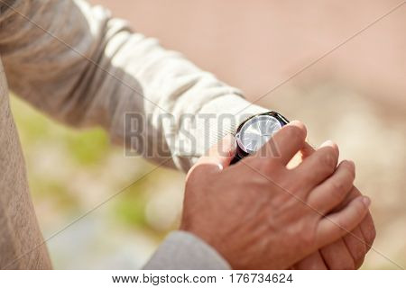 accessory and people concept - senior man checking time on wristwatch outdoors