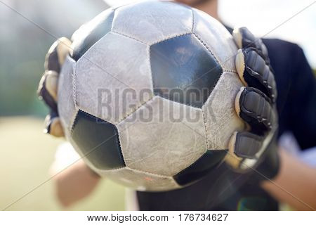 sport and people - close up of soccer player or goalkeeper holding ball at football goal on field