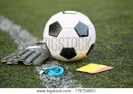 sport, soccer and game - ball, goalkeeper gloves, referee whistle and caution card on football field