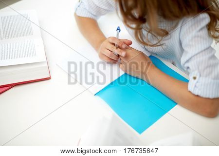 education, people, children and learning concept - girl with book writing to notebook at school