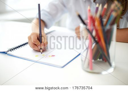 art, creativity, people, childhood and school concept - girl drawing with color pencil or crayon in notebook