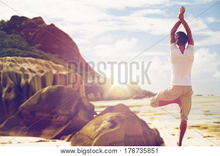 fitness, sport, people and healthy lifestyle concept - man meditating in yoga tree pose over exotic beach background from back