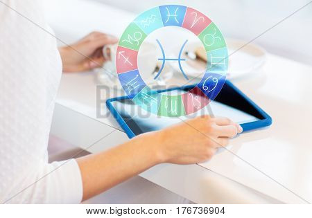 astrology, horoscope, people and technology concept - close up of young woman hands with tablet pc computer and pisces zodiac sign drinking coffee and eating cake at cafe