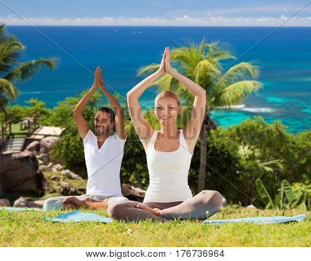 fitness, sport, people and healthy lifestyle concept - smiling couple making yoga in lotus posture sitting on mats outdoors over ocean background