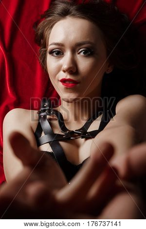 Excited naked submissive woman wearing bdsm fetish lingerie and leather sword belt lying on red and posing to camera