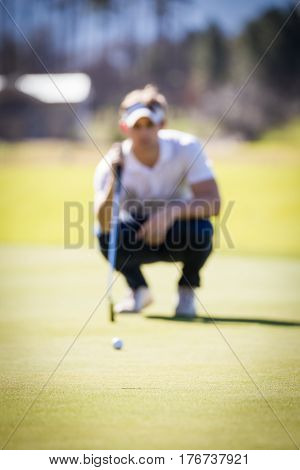 Close Up View Of A Golfer Planning His Shot To The Pin On A Green On A Bright Sunny Day.
