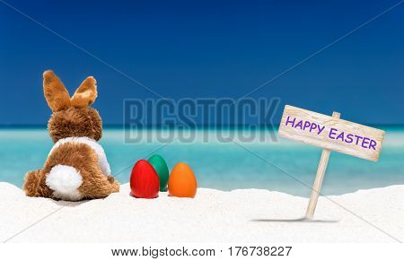 Bunny, easter eggs and Happy Easter sign on a tropical beach